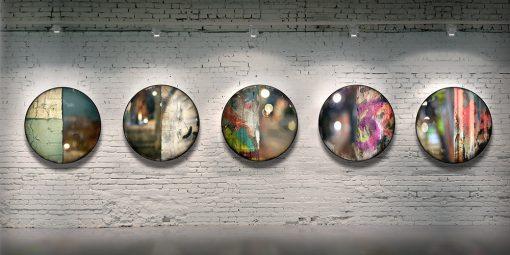 Série CIRCULAIRE en contexte sur mur de brique. Pièces 1 à 5. Technique mixte sur panneau de bois circulaire (photographie nocturne, travail numérique, peinture aérosol et époxy) par l'artiste visuel Pascal Normand.